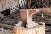 Rustic anvil on wooden stump. — Stock Photo