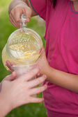 Young girl pouring lemonade from a glass pitcher — Stock Photo
