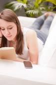 Menina estudando em um sofá — Fotografia Stock