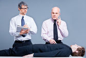 Clerks repairing a businessman for fun — Stock Photo