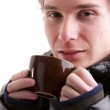 Young man having a hot drink in winter — Stock Photo #57922675
