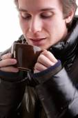 Young man having a hot drink in winter — Stock Photo