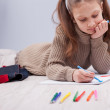 Little girl colouring on her notebook — Stock Photo #58419891
