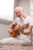 Mature man playing guitar at home — Stock Photo