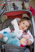 Child girl in herstroller with puppets — Stock Photo