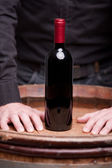 Bottle of red wine and hands of a man — Stock Photo