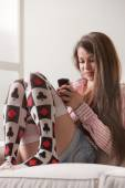 Teen girl on a sofa texting with her phone — Stok fotoğraf