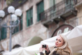 Blonde tourist taking photographs in the city — Stock Photo