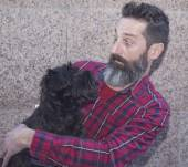 Bearded man sitting with dog — Stock Photo