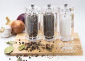 Knoflook, uien, glas molen met peper en zout op een houten bord, geïsoleerd — Stockfoto