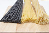 Black and golden spaghetti, pastes  on a wooden board — Stock Photo