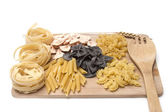 Black and golden macaroni, pastes  on a wooden board — Stock Photo