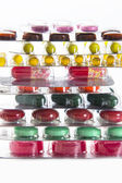 Color tablets, capsules and vitamins in blisters on the white background — Stock Photo