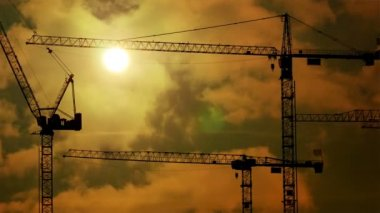Construction cranes at construction site at sunset — Stock Video