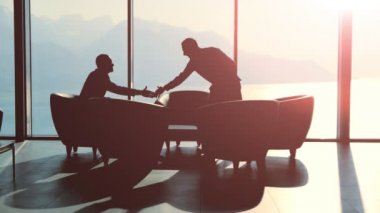 Silhouettes of two businessmen handshaking and talking — Stock Video