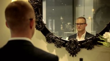 Handsome young businessman wearing glasses looking in the mirror — Stock Video