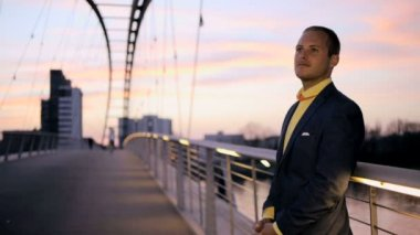 Young businessman in suit standing on the bridge at sunset — Stock Video