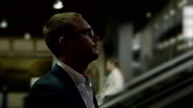 Businessman wearing glasses climbing the escalator — Stock Video
