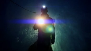 Scientist exploring glacier cave with flashlight — Stock Video