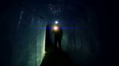Scientist exploring glacier cave with flashlight — Stockvideo