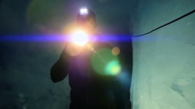 Scientist exploring glacier cave with flashlight — Vídeo de stock