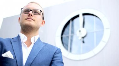 Young businessman looking on the big clock — Stock Video
