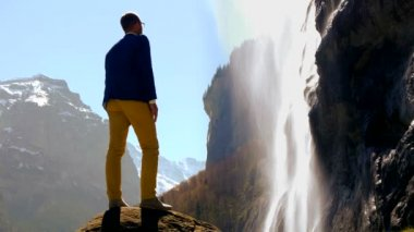 Man standing on stone rock and looking at waterfall. — Stock Video