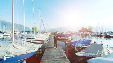 Young businessman standing among the yachts and boats in the marina — Stock Video