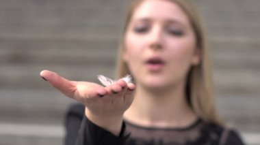 Woman blowing on white feather on the hand — Stock Video