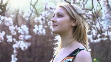 Woman standing under the spring blooming trees — Vídeo de stock