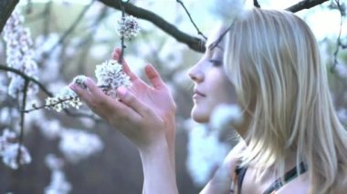 Woman touching and smelling tree blossom — Stock Video