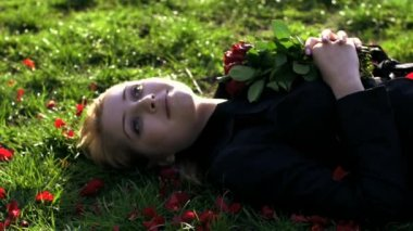 Young woman lying down on the green grass and holding bouquet of roses — Vídeo de stock