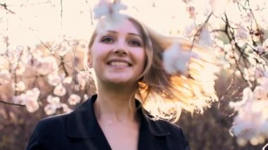 Blond woman spinning around under the blooming tree — Stock Video