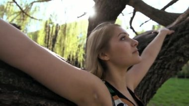Young blond woman standing in front of a tree — Stock Video