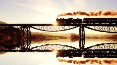 Train crossing bridge at sunset — Stock Video