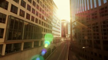 Sun flare shines trough glass buildings — Stock Video