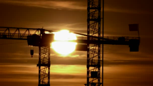 Sun crossing behind crane construction — Vidéo