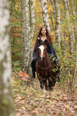 Amazing girl riding a horse without any equipment in autumn fore — Stock Photo