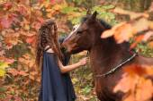 Nice girl with brown horse in autumn — Stock Photo