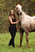 Beautiful girl with nice dress standing next to nice horse — Stock Photo
