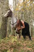 Beautiful girl with nice dress standing next to nice horse — Fotografia Stock