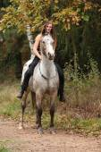 Beautiful girl riding a horse without bridle or saddle — Stock Photo