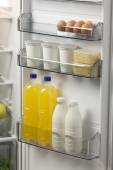 Opened refrigerator full of foodstuff and drinks — Stock Photo