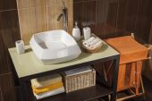 Detail of a modern bathroom with sink, towels and laundry basket — Stok fotoğraf