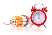 Alarm clock and cigarettes like bomb — Stock Photo
