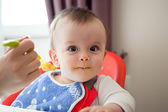Curious smeared with food baby, eating vegetable puree — Stock Photo