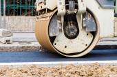 Close up detail of the front wheel of a steamroller working on asphalt lane — Stock Photo