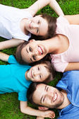 Family lying on grass — Stock Photo