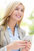 Young woman holding mobile phone — Stock Photo