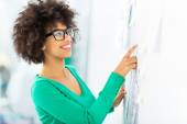 Afro woman looking at wall with adhesive notes — Stock Photo